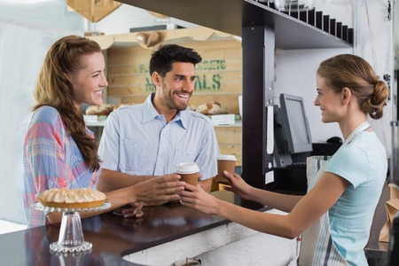 Side view of a smiling waitress giving coffee to a couple at the coffee shop