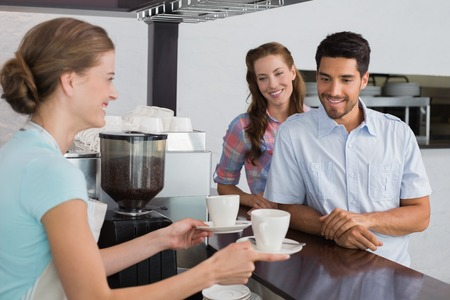 Side view of a smiling waitress giving coffee to a couple at the coffee shop photo