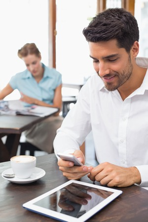 Concentrated young man text messaging in the coffee shop photo