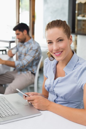 Smiling young woman using laptop and mobile phone in the coffee shop photo
