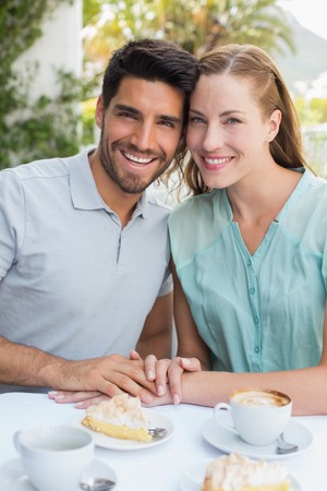 Portrait of a romantic young couple sitting at the coffee shop photo