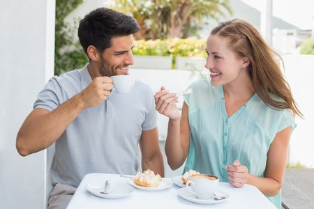 Portrait of a happy young couple sitting at the coffee shop photo