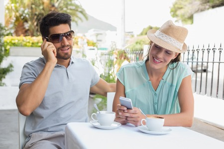 Happy young couple with mobile phones sitting at the coffee shop photo