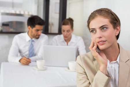 Businesswoman using mobile phone with colleagues in meeting behind at office desk photo