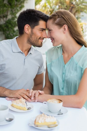 Romantic young couple looking at each other at the coffee shop photo