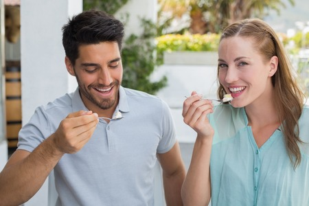 Portrait of a cheerful young couple eating at the coffee shop photo