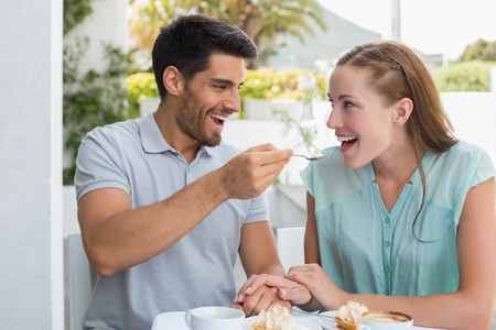 Portrait of a happy young man feeding woman at the coffee shop photo