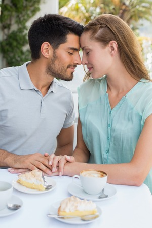 Romantic young couple sitting with eyes closed at the coffee shop photo