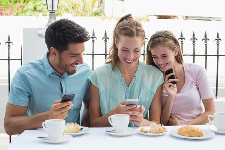 amabilidad: Retrato de tres amigos felices que leen el mensaje de texto en los caf� �