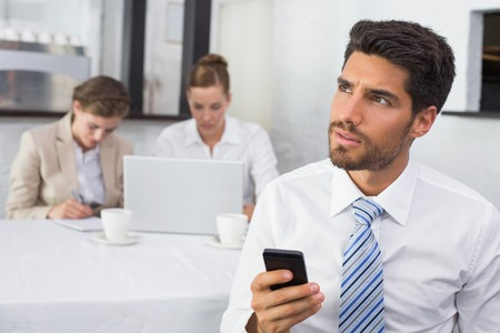 Businessman text messaging with colleagues in meeting behind at office desk photo