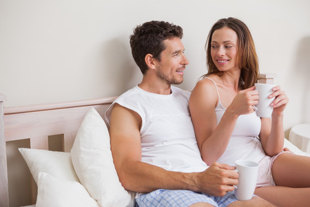 Happy relaxed young couple having coffee in bed at home photo