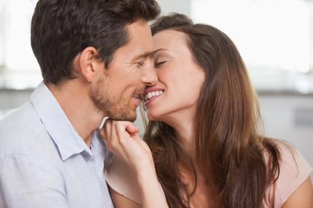 pareja besandose: Vista lateral de una pareja de j�venes amantes a punto de besarse en casa