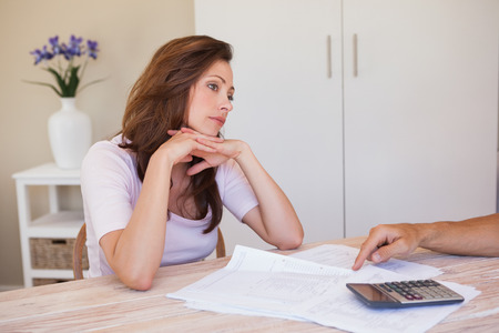 figuring: Angry young woman with hand pointing at home bills on the table at home Stock Photo