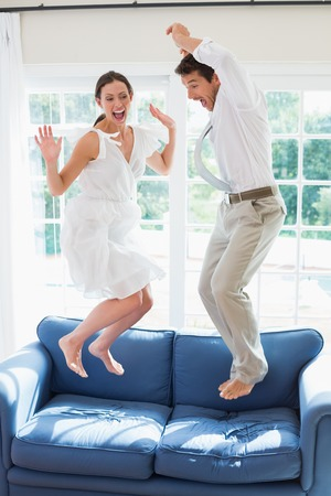 air jump: Side view of a cheerful young couple jumping on couch at home