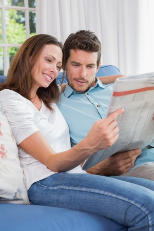 Relaxed happy young couple reading newspaper on couch at home photo