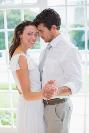 lovers holding hands: Side view of a loving young couple holding hands at home