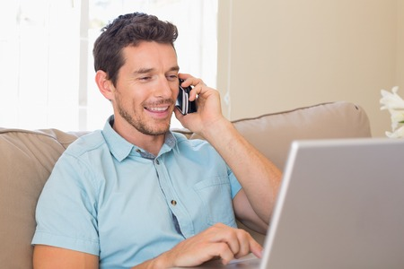 Happy young man using laptop and mobile phone on couch at home