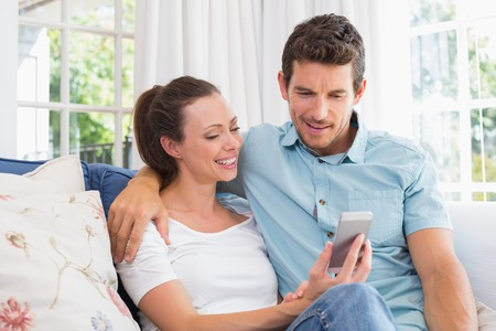 mobile phone adult: Smiling young couple text messaging in the living room at home Stock Photo