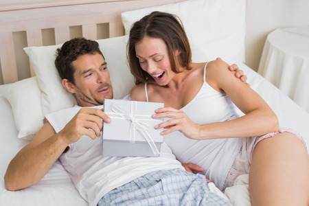 Relaxed young couple with gift box lying together in bed at home photo