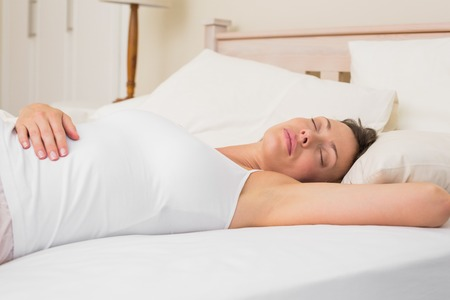 Relaxed young woman sleeping in bed at home photo