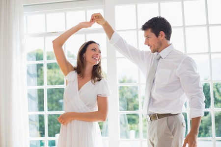 Loving young couple dancing at home