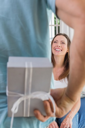 Close-up of a cropped man surprising a happy woman with a gift box at home photo