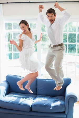 excitement: Side view of a cheerful young couple jumping on couch at home