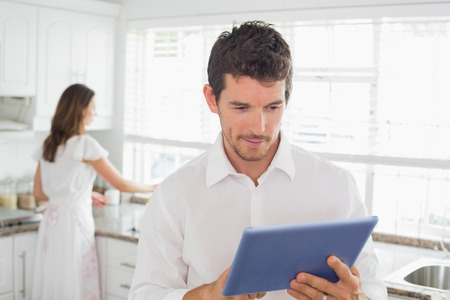 Young man using digital tablet with woman in the background in kitchen at home photo