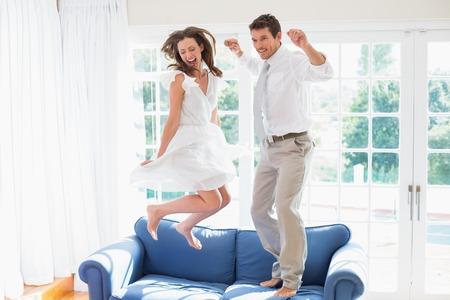 陽気な若いカップルが自宅のソファの上にジャンプの側面図 写真素材 - 28070994