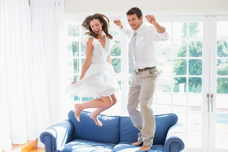 Side view of a cheerful young couple jumping on couch at home