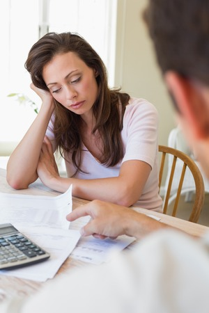 figuring: Upset young woman and man sitting with home bills at the table