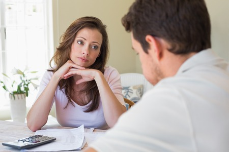 Young woman and man sitting with home bills at the table Stock Photo - 28070815