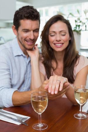 anillo de compromiso: Retrato de una mujer joven feliz que muestra el anillo de compromiso adem�s del hombre en el hogar Foto de archivo