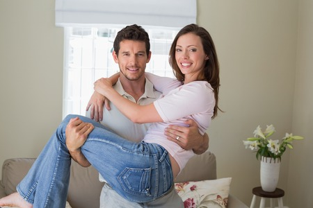 man carrying woman: Portrait of a smiling young man carrying woman at home Stock Photo