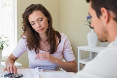 Young woman and man sitting with home bills at the table Stock Photo - 28070706