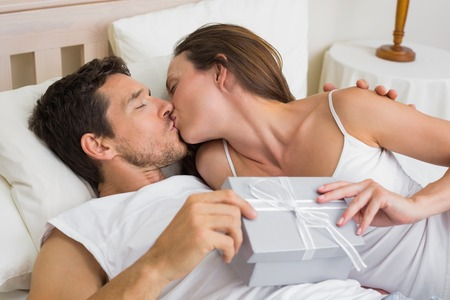 Relaxed young couple kissing with gift box in hand in bed at home photo