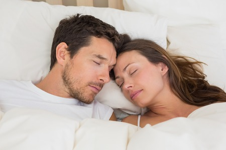 Relaxed young couple sleeping together in bed at home photo