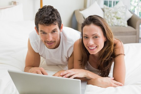 Smiling young couple using laptop in bed at home photo