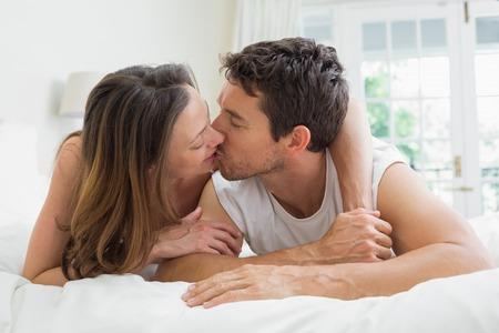 novios besandose: Joven pareja bes�ndose en la cama en su casa