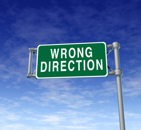 Wrong direction green traffic sign representing new strategy and warning of continued planning of old ideas prompting change and renewal of solutions for business and personal life.