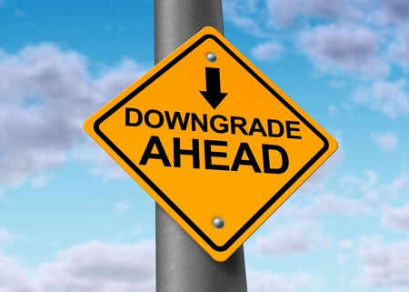 lower value: Downgrade symbol represented by a traffic sign warning that there will be bad news for a company that will result in a lower price for the value of the declining stock.
