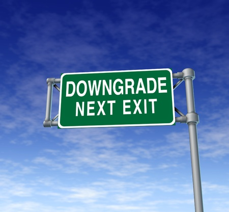 downgrade: Company downgrade symbol on a green highway sign representing the concept of a bad rating on a business that is not profitable and is performing below shareholders expectations.