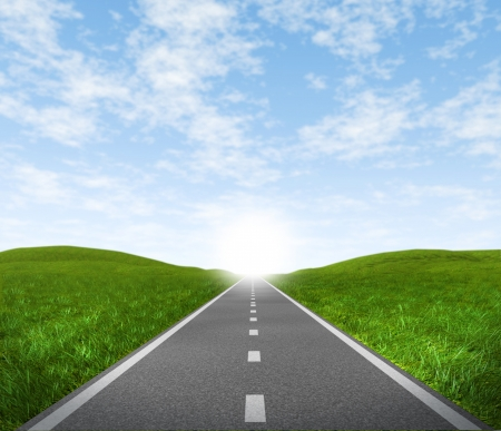 road to success: Open road highway with green grass and blue sky with an asphalt street representing the concept of journey to a focused destination resulting in success and happiness.