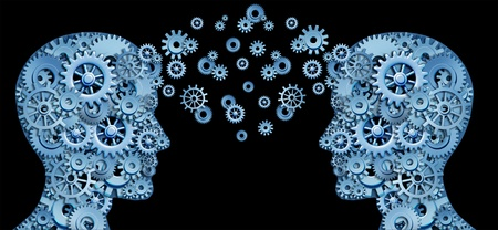 Teamwork and Leadership with education symbol represented by two human heads shaped with gears and cogs representing the concept of intellectual communication through technology exchange. Stock Photo