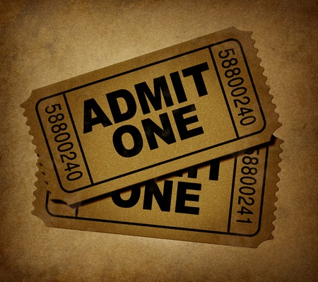 1: movie tickets with vintage grunge texture representing two stubs that admit one for show business price to enter and the cinematic theater entrance fee to go see the movies at the big screen. Stock Photo