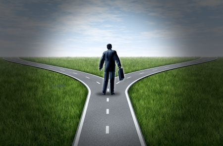 business dilemma: Business man at a cross roads standing at a horizon with grass and blue sky showing a fork in the road representing the concept of a strategic dilemma choosing the right direction to go when facing two equal or similar options.