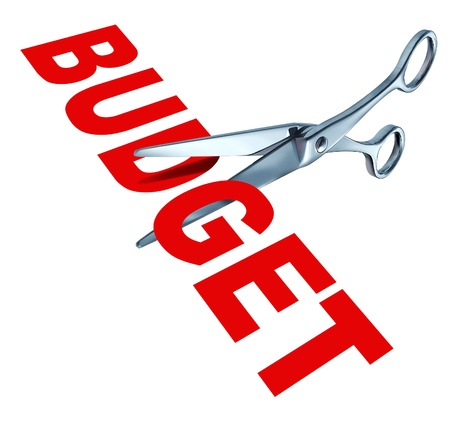 taxes budgeting: Budget cuts symbol for reducing budgeted expenditures by slashing costs and eliminating financial surplus represented by sharp open metal scissors.