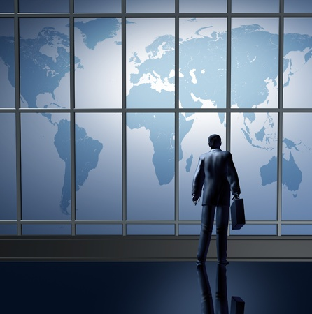 Business traveling international represented by an airport departure waiting at the terminal lounge represented by a businessman standing with a breifcase in front of large glass windows looking at a global map of the world. photo