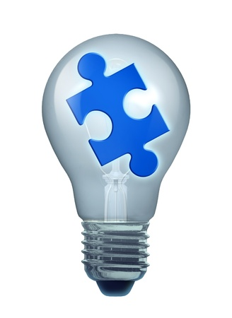 Ideas and solutions symbol represented by an isolated light bulb and a puzzle piece.