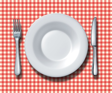 Place setting for a family restaurant with a red and white checkered table cloth with a ceramic china plate silver fork and knife as a symbol of fine italian food cuisine and traditional americana fast food eateries. photo